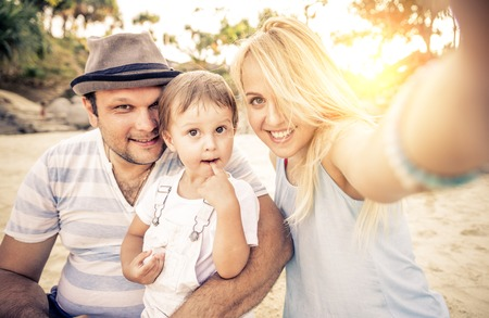dad: Mom and dad playing with their handsome son - Family and baby outdoors - Young beautiful mother taking a self portrait with her family Stock Photo