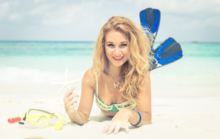 airiness: woman lying on the sand holding starfish and wearing fins. concept about summer and vacations