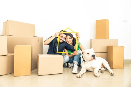 Happy couple with dog moving to a new home - Cheerful family starting a new life - Multi ethnic couple of lovers buy new apartment Banco de Imagens