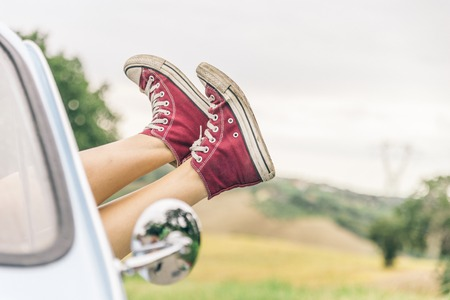 sex girl: Woman relaxing in her car while driving in the countryside - Young  cool girl with shoes out of the automobile window to enjoy the view Stock Photo