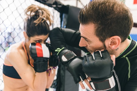 kickboxing: mma training. couple making sparring in the mma cage. concept about fighting, fitness and sport