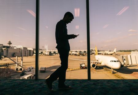 airport window: Young man checking his phone while waiting his flight in the airport - Business man at airport and airplane and airport in the background Stock Photo