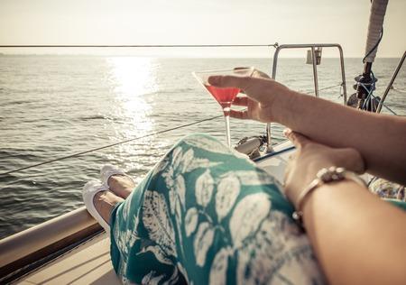 donna ricca: donna, bere cocktail sulla barca. Concetto su tempo libero, l'estate, le vacanze e la gente