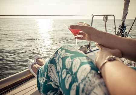 lady: woman drinking cocktail on the boat. concept about leisure, summer, vacations and people