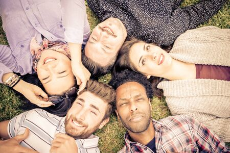 airiness: group of friends lying on the grass. concept about students,people, carefree and relaxation Stock Photo
