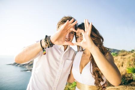 haciendo el amor: Pareja de enamorados haciendo una forma de coraz�n con las manos - Amantes en una cita rom�ntica al aire libre - Conceptos sobre el amor, la boda, la relaci�n Foto de archivo