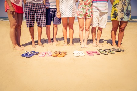 Group of friends on the beach with colored slippers on the sand - Tourists on vacation on a tropical beach during summertime