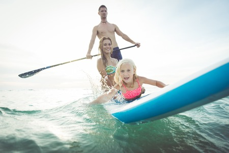 family making paddle surf in the ocean. concept about sport, healthy lifestyle and people Stock Photo