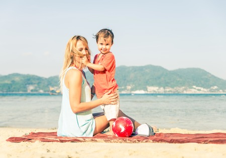 mom son: Mom playing with her handsome son on the beach - Happy family on vacation on a tropical beach Stock Photo