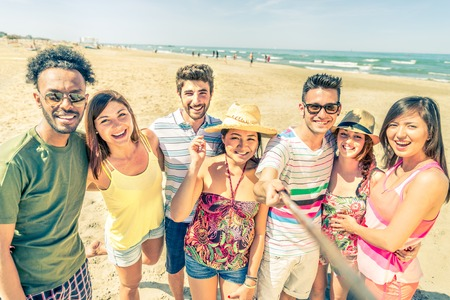 Multiethnic group of friends enjoying vacation  and taking a picture with selfie stick - Mixed group of several people having fun on the beach