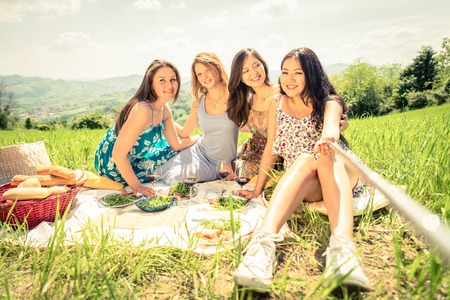 rural: Multi-ethnic group of women enjoying picnic in the countryside and taking a picture with selfie stick - Four girls on vacation having fun