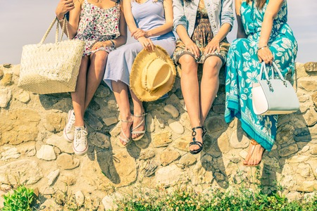 Cztery dziewczyny siedzi na ścianie na zewnątrz z wiosną i latem dressware - Kobiety spotkania i zabawy w wsi - Pojęcia o przyjaźni, sezonowych, stylu życia i zakupy