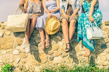 amicizia: Quattro amiche si siedono su un muro esterno con la primavera e l'estate dressware - Donne meeting e divertirsi in un paesaggio - Concetti di amicizia, di stagione, lo stile di vita e lo shopping Archivio Fotografico