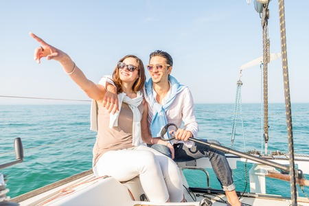 blue romance: Beautiful couple of lovers sailing on a boat - Young attractive man holding rudder of a yacht and looking far away - Two fashion models posing on a sailing boat at sunset Stock Photo