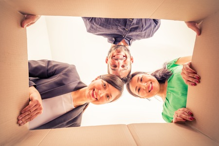 forniture: Group of friends moving to new apartment and unpacking boxes -  Happy people looking inside a box Stock Photo
