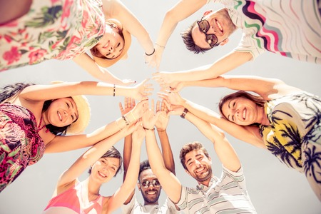 Group of friends in circle looking down and rising hands - Several people exulting on the beach at sunset - Concepts about summer,lifestyle and happiness Stock Photo