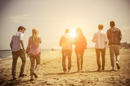 Gruppo multi-etnico di amici a piedi sulla spiaggia e parlando - Gruppo di giovani adulti sagome al tramonto Archivio Fotografico