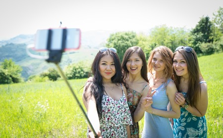 group of girls making selfie with selfie stick. concept about friendship,nature,technology, and people Stock Photo