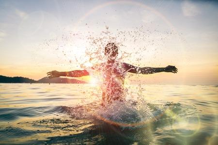 Man Spritzwasser während der Sommerferien - Junge attraktive Mann, die Spaß auf einem tropischen Strand bei Sonnenuntergang Standard-Bild