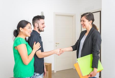 Makler einen Vertrag zu schließen. Familie Kauf neuer Wohnung nach chosing es. Konzept über Häuser, Unternehmen und Personen