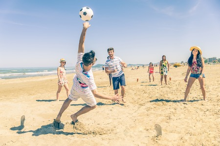 girl kick: Group of multiethnic friends playing soccer on the beach - Football match on the sand on summertime - Tourists having fun on vacation with beach games Stock Photo