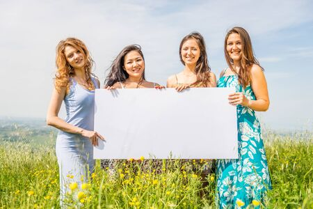 advertising sign: Group of multiethnic girls holding blank advertising board in a flowers field - Four beautiful and happy women promoting something with white billboard Stock Photo