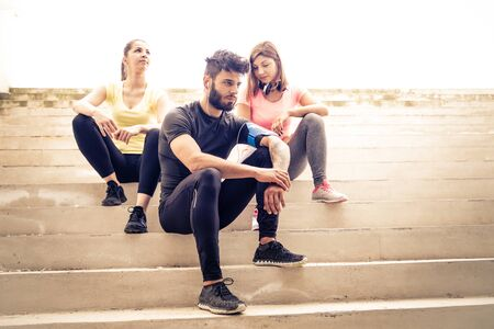 muscled: Team of urban runners getting ready for training - Muscled man and sportive women with sportwear sitting on stairs  - Friends working out to keep fit and healthy