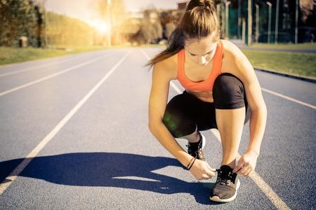 deportista: Mujer juguetona joven que consigue listo para empezar a correr entrenamiento - Atleta corriendo al aire libre al atardecer - Atractiva chica haciendo deporte para perder peso y mantenerse en forma