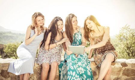 millennial: group of girls watching tablet outdoor. concept about technology, carefree, and people