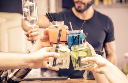 amicizia: brindisi con coktails occhiali. concetto di vita notturna, alcool, amicizia, bartending, divertimento, e la gente
