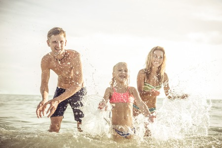 6 people: playful family spraying water and having fun. concept about vacation, summer,fun, family and people. Stock Photo