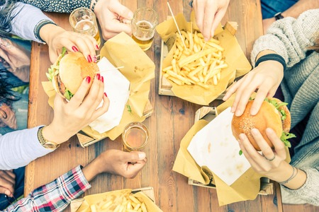 people eating restaurant: Group of friends toasting beer glasses and eating at fast food - Happy people partying and eating in home garden - Young active adults in a picnic area with burgers and drinks Stock Photo
