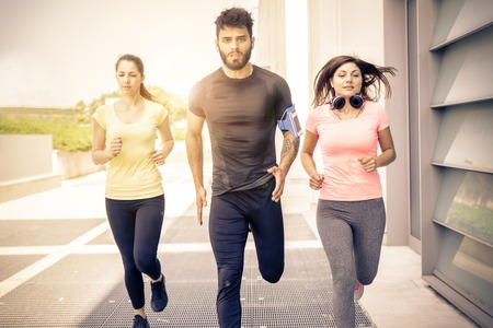 Team of urban runners training - Muscled man and sportive women with sportwear running on the streets  - Friends working out to keep fit and healthy Stock Photo