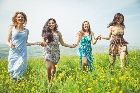 airiness: four girls running in the fields. concept about spring time,happiness,nature, women and people