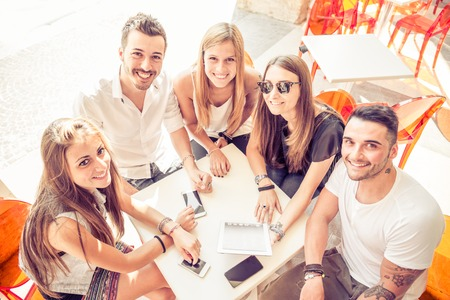 Группа счастливых улыбающихся друзей и сидел в баре и глядя в камеру, множество цифровых устройств на столе - группа студентов встретиться в кафе на открытом воздухе