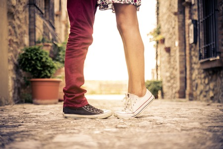 girls kissing girls: Couple kissing outdoors - Lovers on a romantic date at sunset,girls stands on tiptoe to kiss her man - Close up on shoes Stock Photo