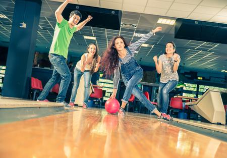 Группа друзей на боулинг - Молодые люди веселятся на боулинг, одна девушка бросает мяч и друзья поддерживает ее