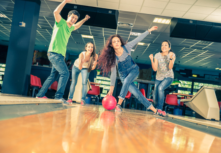 bowling pin: Group of friends at bowling - Young people having fun at bowling,one girl is throwing ball and friends supports her