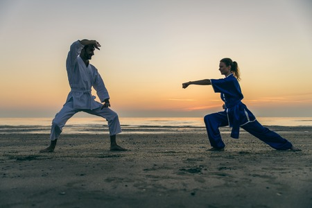 viet vo dao: Two martial arts athletes training  on the beach at sunrise - Sportive man and woman ready to fight - Kung fu and karate masters