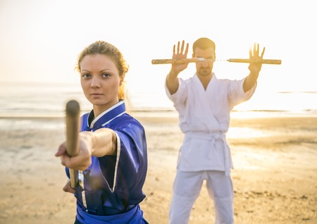 viet vo dao: Two martial arts athletes training with weapons on the beach at sunrise - Sportive man and woman with stick and nunchaku - Kung fu and karate masters