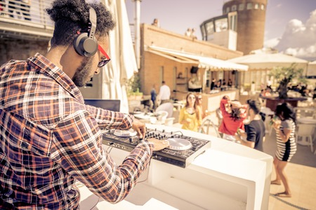DJ는 야외 클럽에서 유행 음악을 연주 - 사람들은 춤과 파티 디스크 자키 여름 콘서트에서 두 곡의 트랙을 혼합하는 동안
