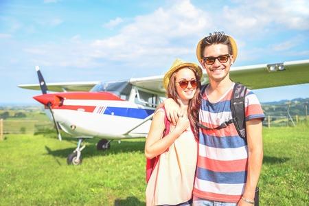 amadores: Pareja de amantes que toman un avión chárter - Los turistas en vacaciones a la espera de su vuelo para ir de excursión - Gente sonriendo y avión privado en el fondo