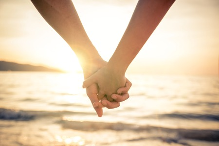 바다 위에 아름다운 일몰에 그들의 손을 잡고 연인 커플 - 로맨틱 한 휴가에 신혼 부부