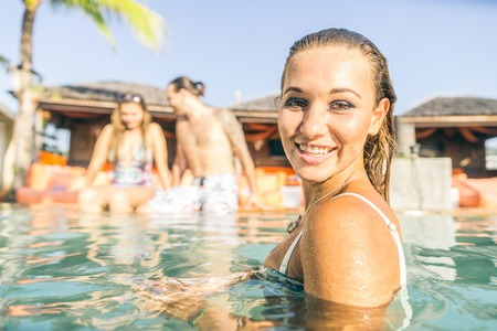Portrait of beautiful young woman while swimming on a swimming pool with her friends - Tourists on vacation in a beautiful tropical resort during summertime