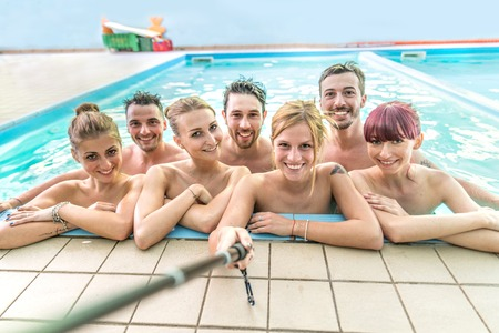 Group of best friends taking selfie with stick in a swimming pool - Several young and attractive people having fun and partying on summer vacation - Girl holding selfie stick and photographing her friends