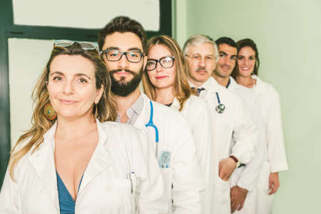 docs: Group of doctors with white coat in a row - Docs of diverse age in a hospital