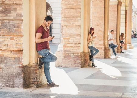 to browse: Young people looking down at cellular phone - Teenagers leaning on a wall and texting with their smartphones - Concepts about technology and global communication