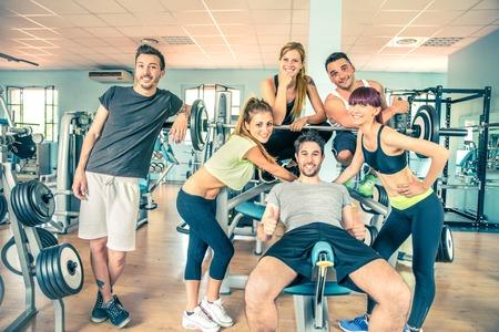 Grupo de pessoas em um ginásio esportivo - amigos alegres felizes em uma sala de musculação enquanto formação - Conceitos sobre estilo de vida e esporte em um clube de fitness