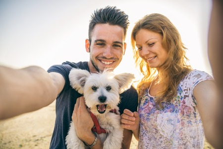Портрет молодой счастливой пары с собакой принимая selfie - Lovers на романтическое свидание на пляже на закате