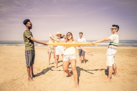 Group of happy and playful friends playing at limbo on the beach - Tourists on vacation on a tropical travel destination on summertime